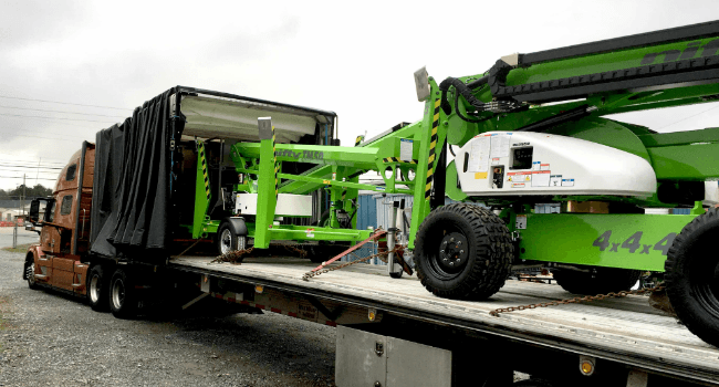 Boom lifts on conestoga trailer in transit