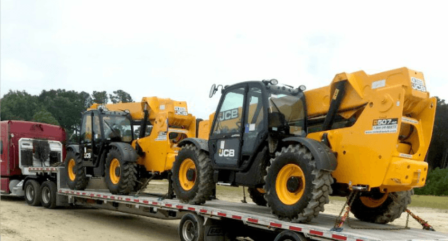 Forklifts on stepdeck trailer in transit